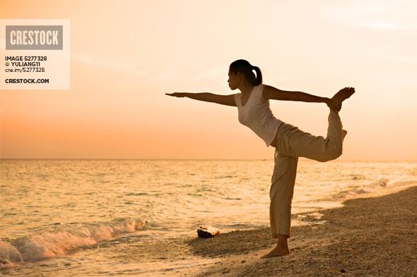 Girl silhouette performing yoga on beach